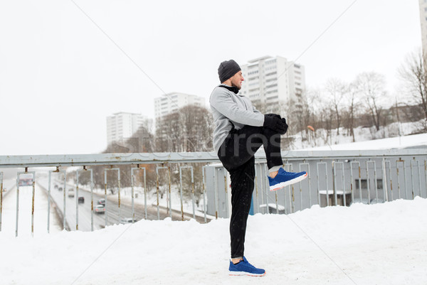 Stock photo: man exercising and stretching leg on winter bridge
