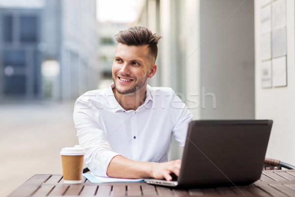 smiling man with laptop and coffee at city cafe Stock photo © dolgachov