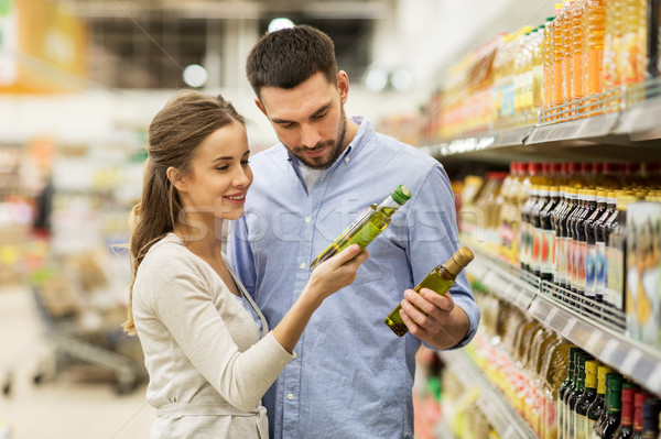 happy couple buying olive oil at grocery store Stock photo © dolgachov