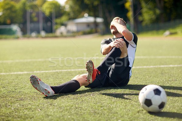 injured soccer player with ball on football field Stock photo © dolgachov