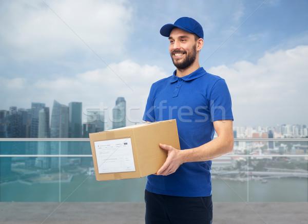 happy delivery man with box over singapore city Stock photo © dolgachov