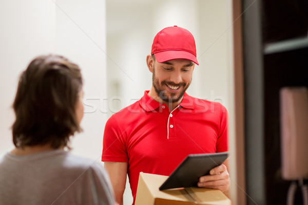 deliveryman with tablet pc and box at customer Stock photo © dolgachov