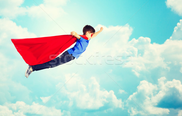 boy in red superhero cape and mask flying over sky Stock photo © dolgachov