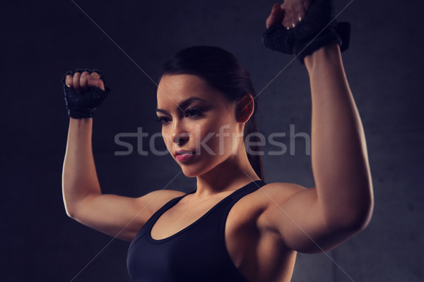 young woman flexing muscles in gym Stock photo © dolgachov