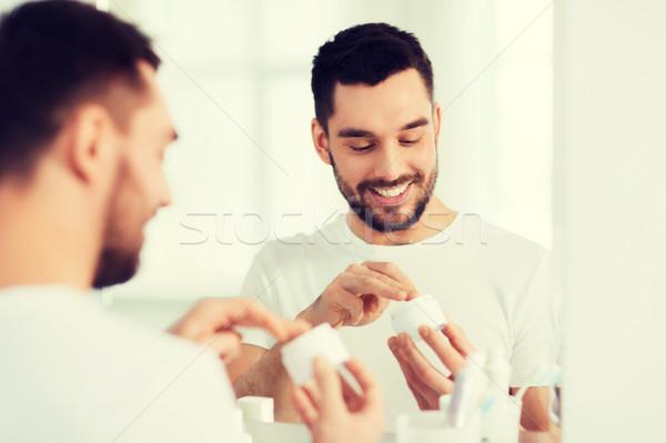 happy young man applying cream to face at bathroom Stock photo © dolgachov