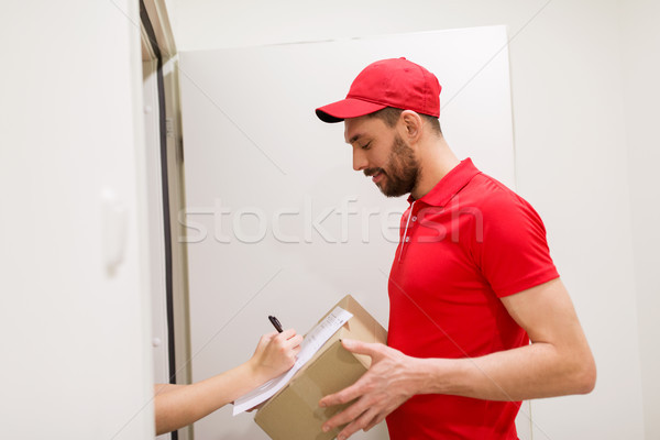 delivery man with box and customer signing form Stock photo © dolgachov