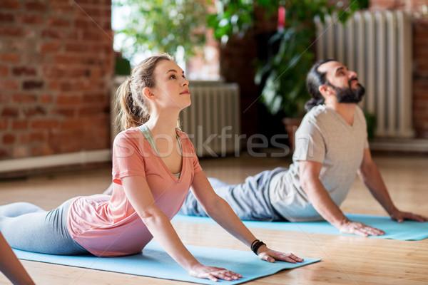 Homem mulher ioga cobra pose estúdio Foto stock © dolgachov