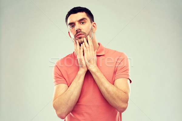 young man touching his face over gray background Stock photo © dolgachov