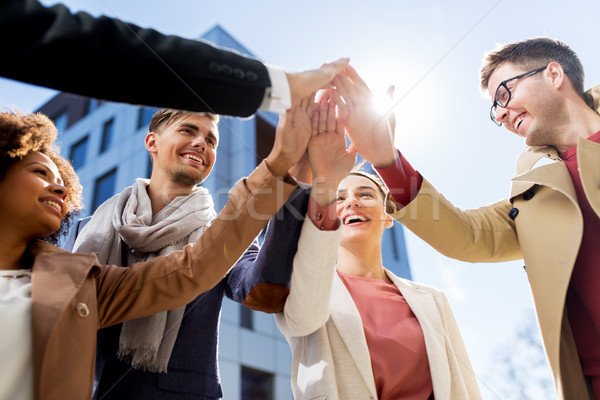 group of happy people making high five in city Stock photo © dolgachov