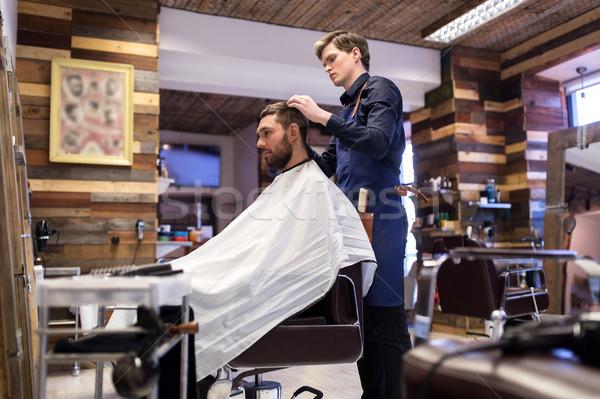 man and barber styling hair at barbershop Stock photo © dolgachov
