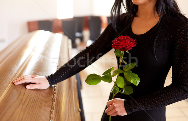 woman with red roses and coffin at funeral Stock photo © dolgachov