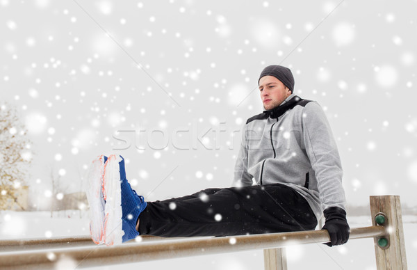 young man exercising on parallel bars in winter Stock photo © dolgachov