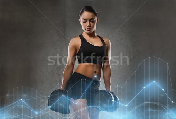 Jeune femme muscles haltères gymnase fitness sport Photo stock © dolgachov