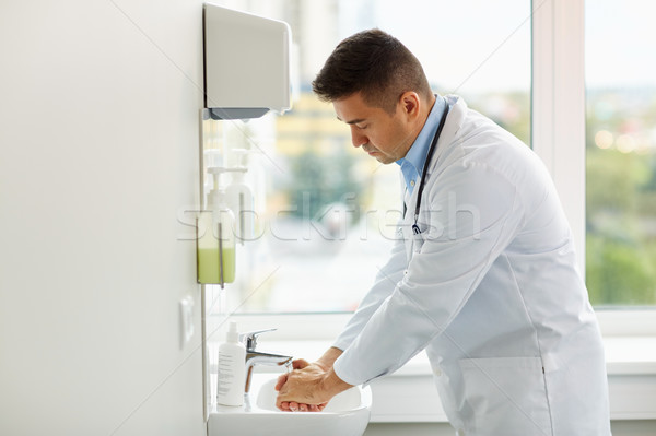 doctor washing hands at medical clinic sink Stock photo © dolgachov
