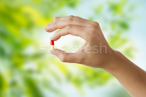 close up of hand holding capsule of medicine Stock photo © dolgachov