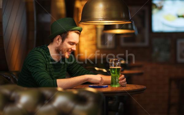 Uomo smartphone verde birra bar pub Foto d'archivio © dolgachov