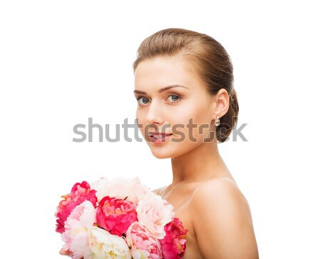 woman wearing earrings and holding flowers Stock photo © dolgachov