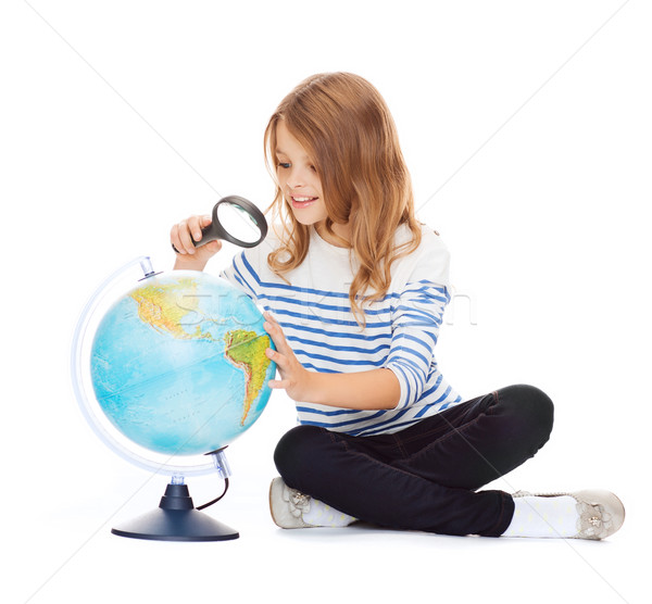 child looking at globe with magnifier Stock photo © dolgachov