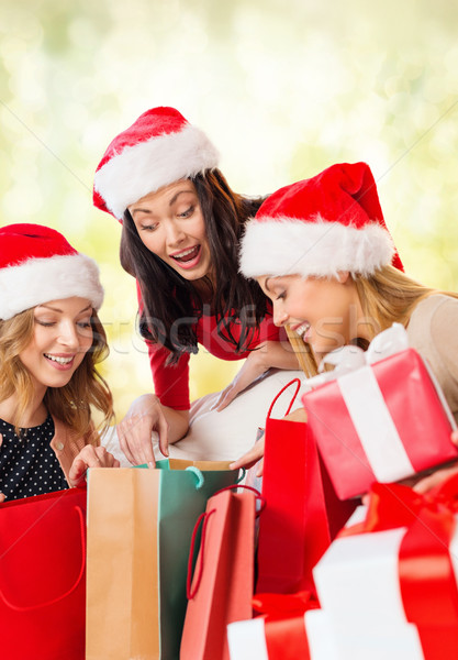 women in santa helper hats with shopping bags Stock photo © dolgachov