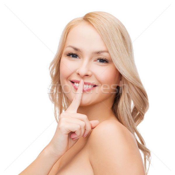 beautiful young woman pointing finger to lips Stock photo © dolgachov