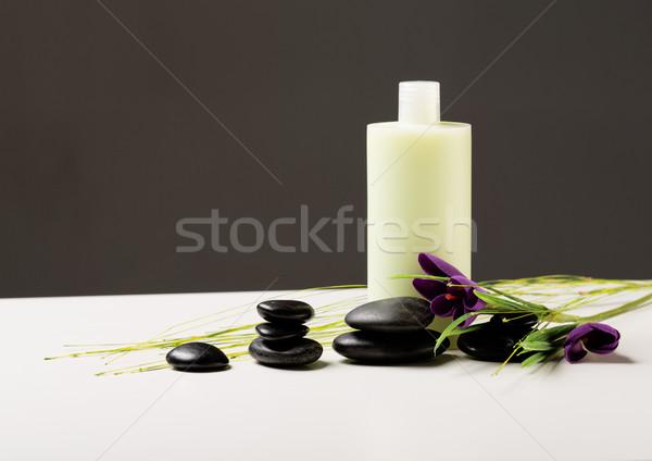 Sampon üveg masszázs kövek írisz virág Stock fotó © dolgachov