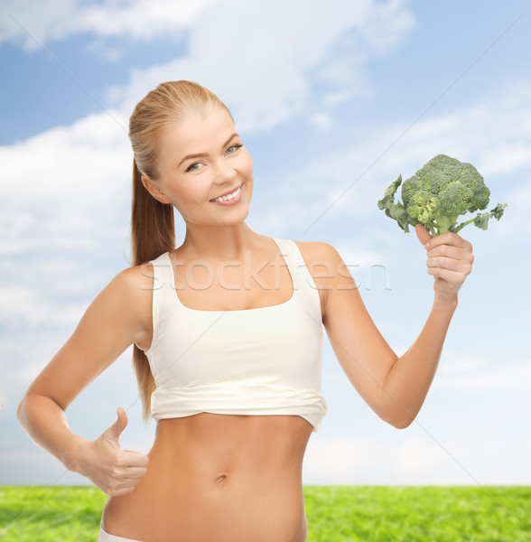 Stock photo: woman pointing at her abs and holding broccoli