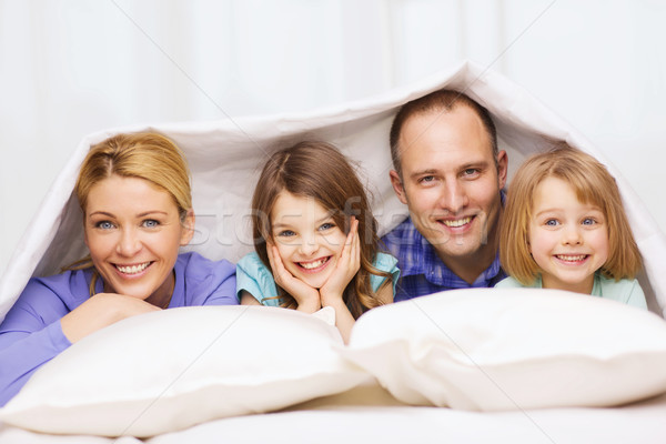 Stock photo: happy family with two kids under blanket at home