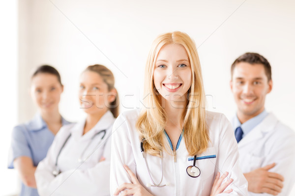 female doctor or nurse in front of medical group Stock photo © dolgachov
