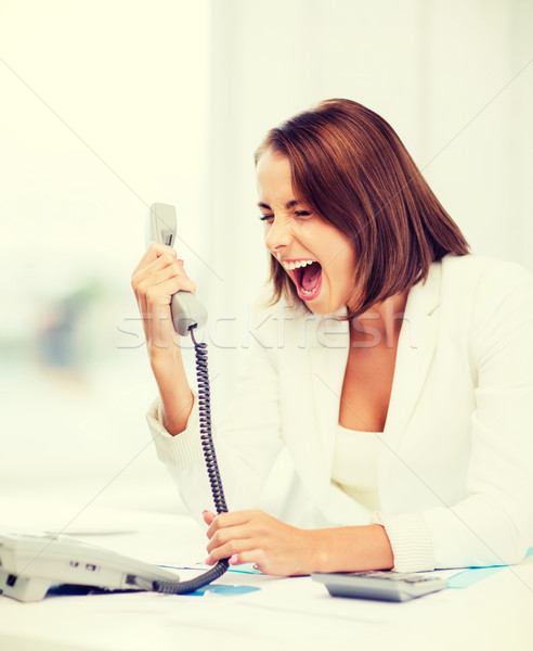 woman shouting into phone in office Stock photo © dolgachov