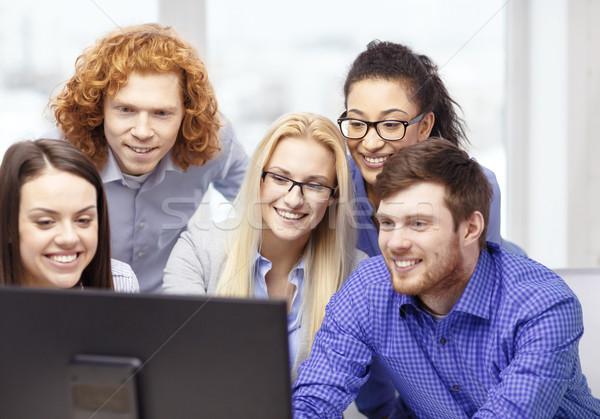Gülen iş ekibi bakıyor bilgisayar monitörü iş ofis Stok fotoğraf © dolgachov