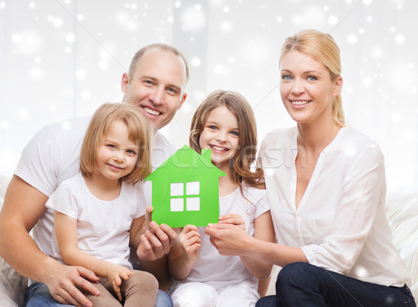 Stock photo: happy family with two kids and paper house at home