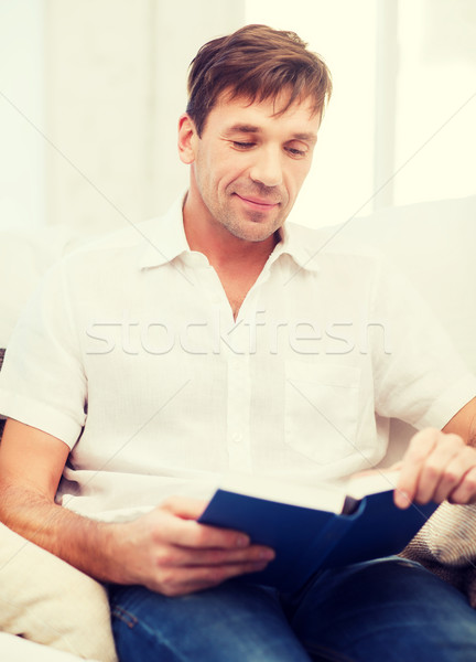 happy man with book at home Stock photo © dolgachov