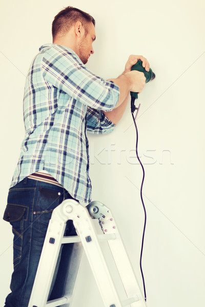 man with electric drill making hole in wall Stock photo © dolgachov