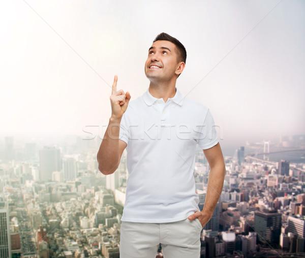 smiling man pointing finger up over city Stock photo © dolgachov