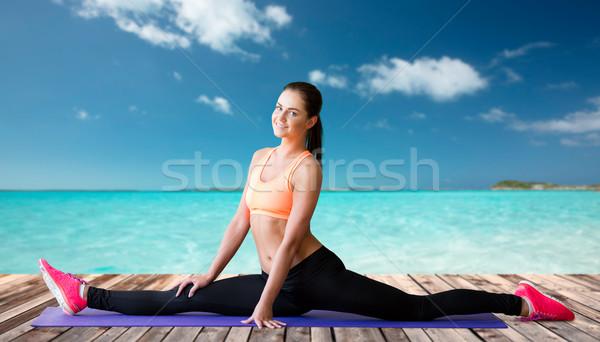 smiling woman doing splits on mat over sea Stock photo © dolgachov