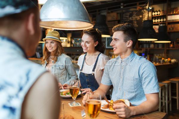 Feliz amigos comer potable bar pub Foto stock © dolgachov