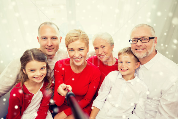 smiling family with selfie stick photographing Stock photo © dolgachov
