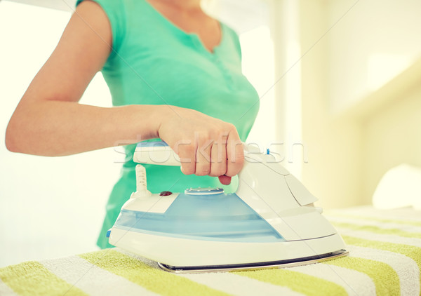 close up of happy woman with iron ironing at home Stock photo © dolgachov