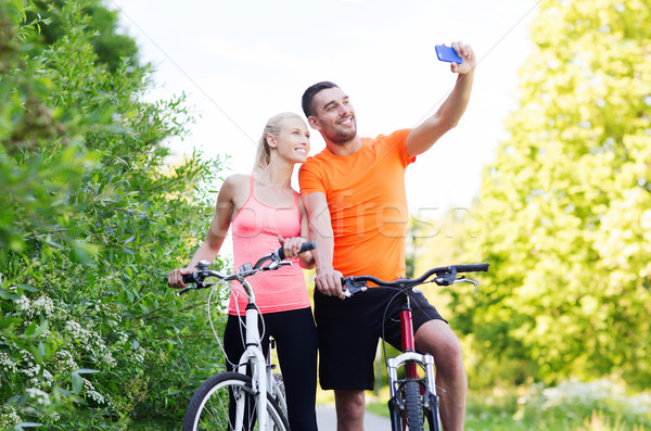 couple with bicycle taking selfie by smartphone Stock photo © dolgachov