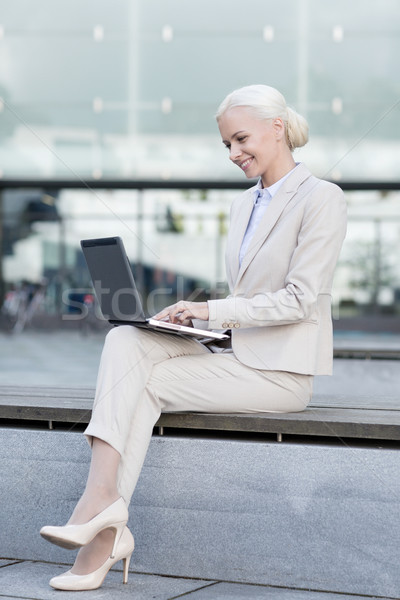 Stock photo: smiling businesswoman working with laptop outdoors