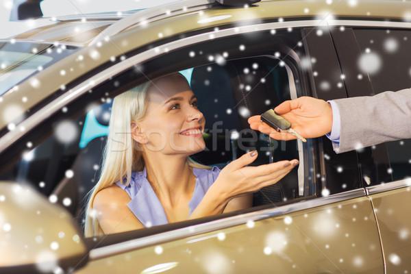 happy woman getting car key in auto show or salon Stock photo © dolgachov