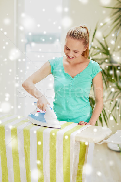 happy woman with iron and ironing board at home Stock photo © dolgachov