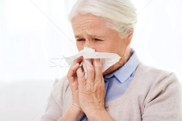 sick senior woman blowing nose to paper napkin Stock photo © dolgachov