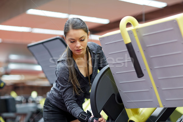 young woman adjusting leg press machine in gym Stock photo © dolgachov
