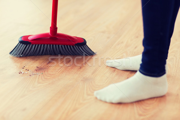 close up of woman legs with broom sweeping floor Stock photo © dolgachov