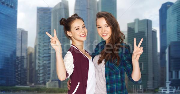 Gelukkig tienermeisjes tonen vrede teken Stockfoto © dolgachov