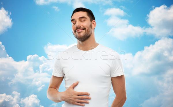 happy full man touching tummy over blue sky Stock photo © dolgachov