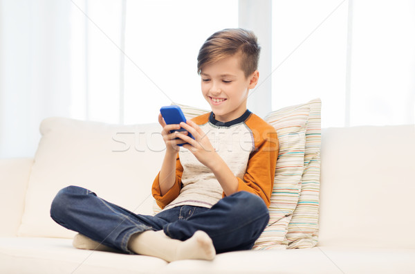 boy with smartphone texting or playing at home Stock photo © dolgachov