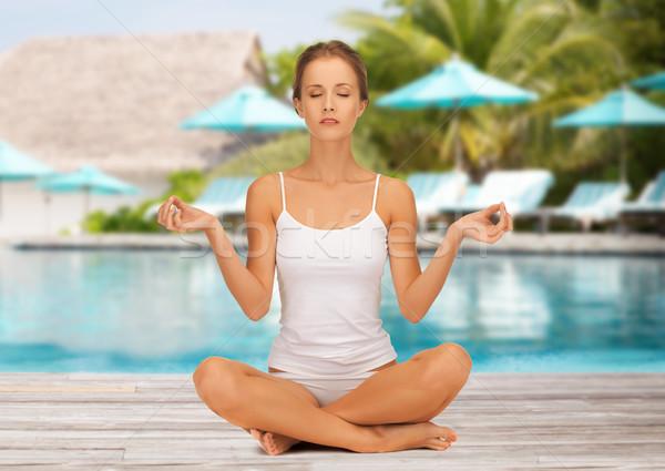 woman practicing yoga lotus pose over beach pool Stock photo © dolgachov