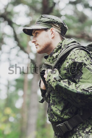 close up of soldier or hunter with gun in forest Stock photo © dolgachov